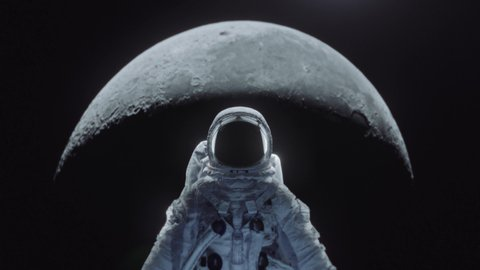 Dolly shot of an astronaut in spacesuit with moon in the background.