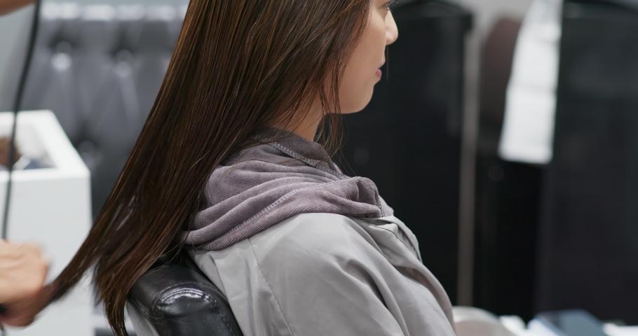 Woman blowing hair in the salon | Shutterstock HD Video #1035409271