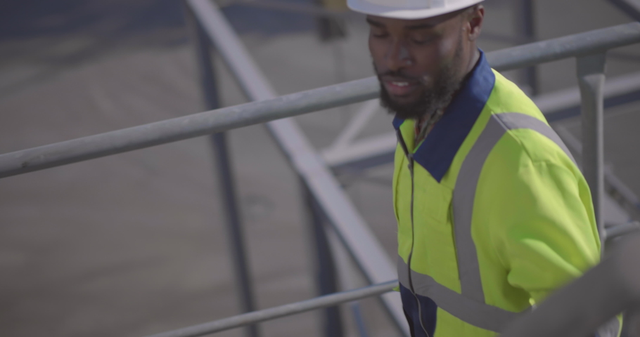 Close up of african-american engineer climbing safety ladder at construction site #1035420335