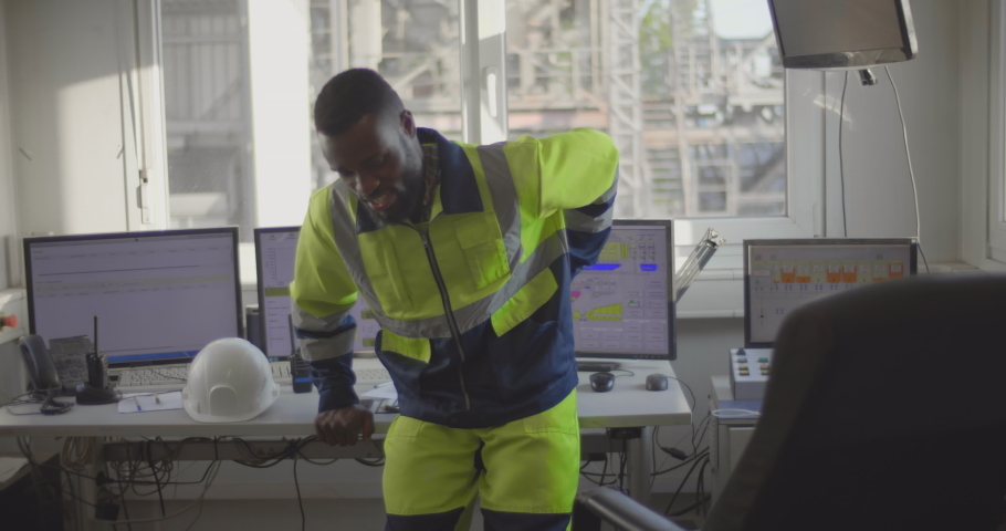 Portrait of young african industrial worker suffering from backache, touching back with hand standing in control room