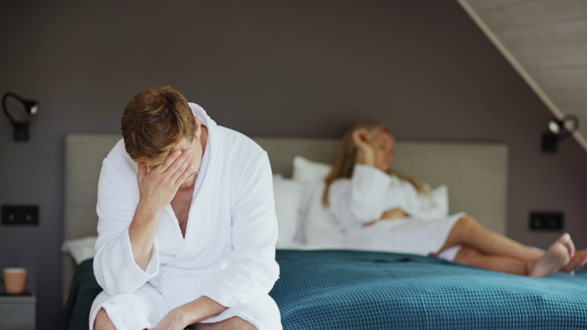 Frustrated middle aged man in white bathrobe sitting on bed after sexual failure or adultery and rubbing forehead, female partner lying in background. Man raising head and looking at camera