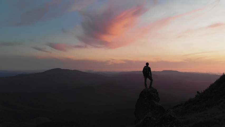 Person standing on rock with epic mountain viewpoint with a colorful sunset drone aerial landscape shot