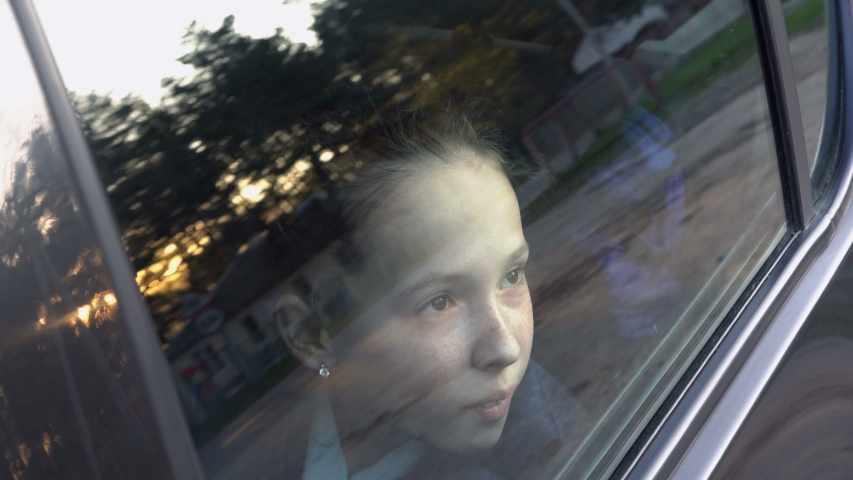 Close-up of the face of a cute little girl who looks thoughtfully through the glass of the car at the sky and sunset. The glass reflects the setting sun and the trees. Shooting outside the car. 4K