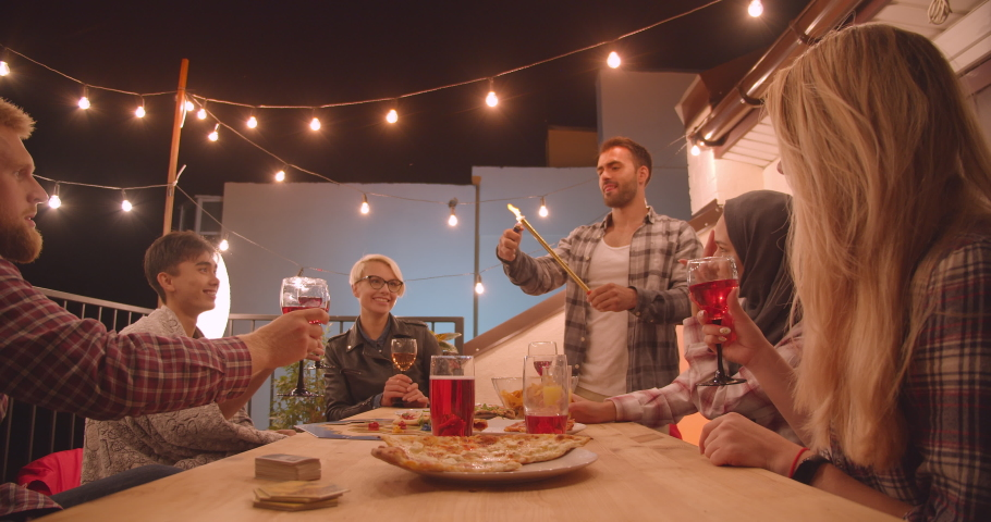 Closeup portrait of diverse multiracial group of friends eating pizza and drinking wine with firework stick at cool party in cozy evening #1035467096