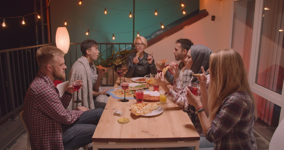 Closeup portrait of group of friends eating pizza celebrating at cool party in cozy evening with fairy lights on background #1035467111
