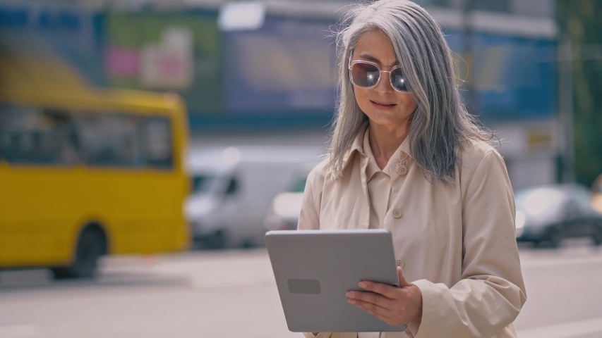 Middle-aged Business Woman Is Standing In The City Center And Using Her Tablet.She Is Wearing Stylish Sunglasses.The Cars Are Passing By Her.Sometimes The Lady Looks Aside
