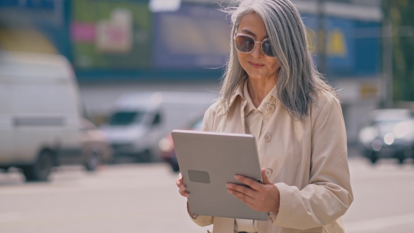 Middle-aged Business Woman Is Standing In The City Center And Using Her Tablet.She Is Wearing Stylish Sunglasses.The Cars Are Passing By Her