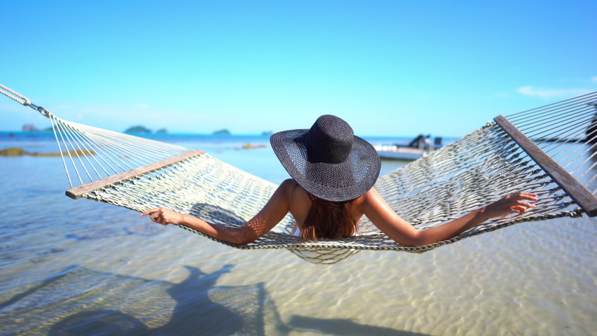 Young woman wearing a floppy black straw hat sitting in the sun and swinging in a hammock while looking out at the ocean.