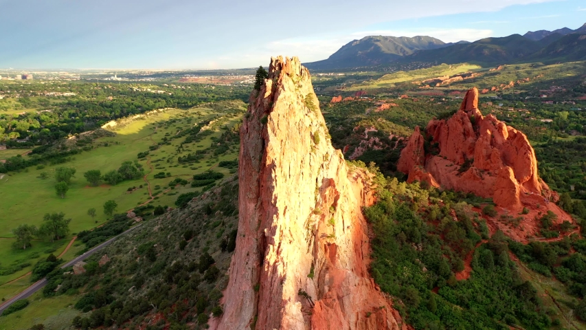 Aerial, drone shot, panning around the famous, red sandstone mountains, at the Garden of the Gods park, on a sunny evening, in Colorado springs, USA