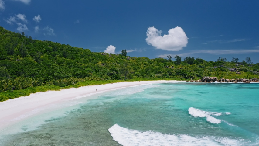 Aerial view of tropical paradise beach Anse Coco. Unrecognized lone tourist couple walk on white sand coast with blue blue lagoon and rolling waves. La Digue island, Seychelles