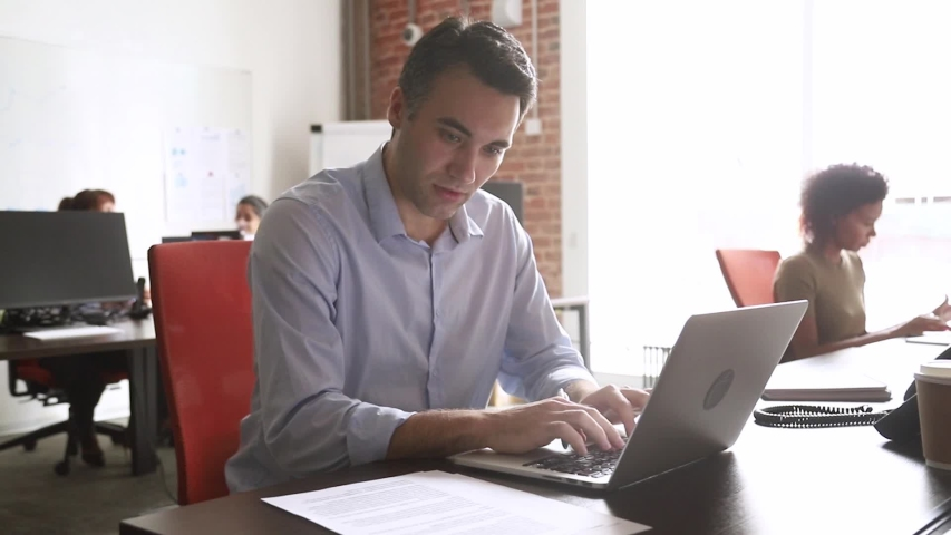 Middle aged employee read agreement document typing on laptop prepare report having busy fruitful day in shared office room coworking space, check contract terms texting making adjustments using pc | Shutterstock HD Video #1035500576