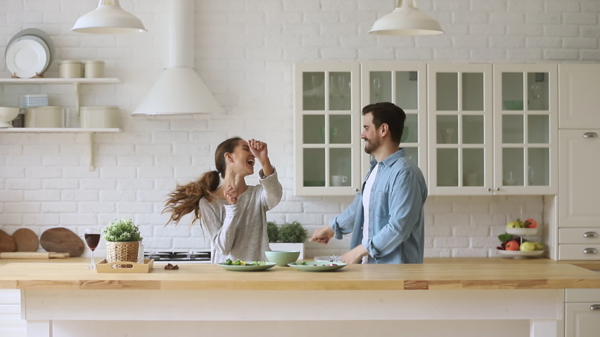 Young happy active family couple dancing laughing together preparing food at home, carefree joyful husband and wife having fun cooking healthy romantic dinner meal listen to music in modern kitchen #1035500636