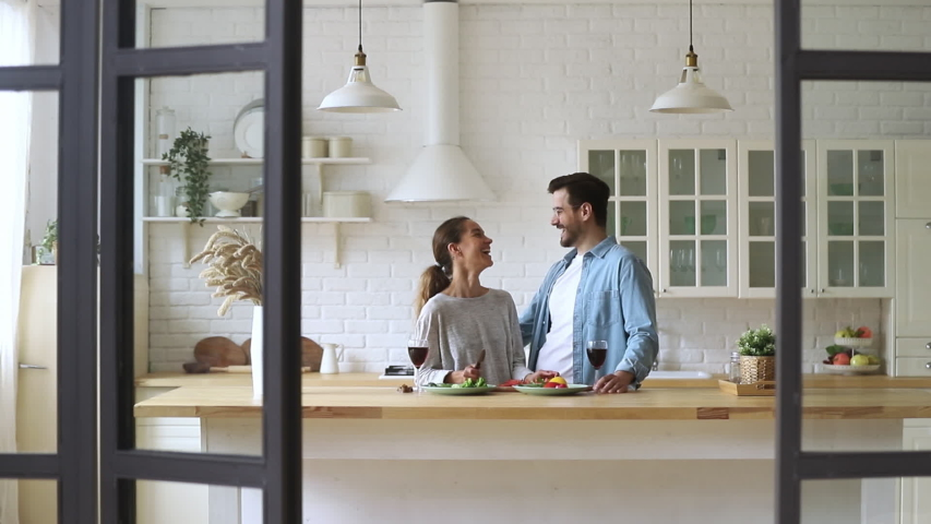 Happy loving young family couple cutting fresh vegetable salad having fun cooking together in modern cozy kitchen interior, smiling husband and wife bonding laughing helping prepare healthy meal #1035500735