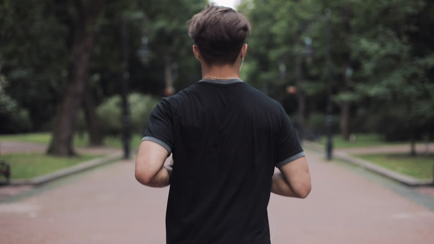 Caucasian Young Man in Headphones Running in Park Back Side View Concept Healthy Lifestyle. | Shutterstock HD Video #1035502241