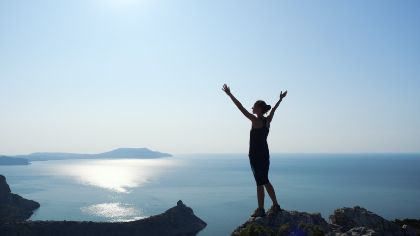Young inspired woman raises her hands up standing on the top of a mountain above the sea against beautiful blue sky. Silhouette of a happy hiker woman standing on the summit.   Shutterstock HD Video #1035506279