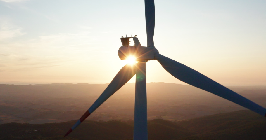Aerial close up shot of wind mills rotating by the force of the wind and generating renewable energy in a green ecologic way to the planet on a sunset. Royalty-Free Stock Footage #1035507986