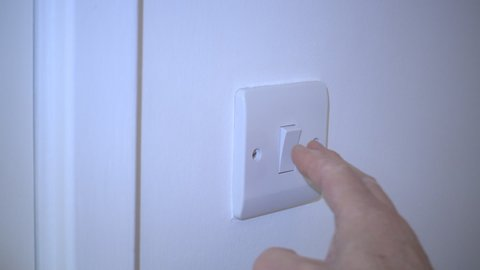 Close POV slow motion shot of a man's hand closing an interior door, then using a wall switch to turn on a light in a white room.