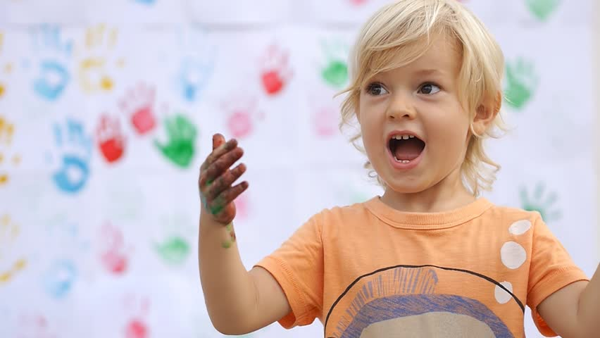 "Amazing cute happy child surprising, saying wow and rubbing color paint on his little hands on color handprints background 50fps"" #10355165"