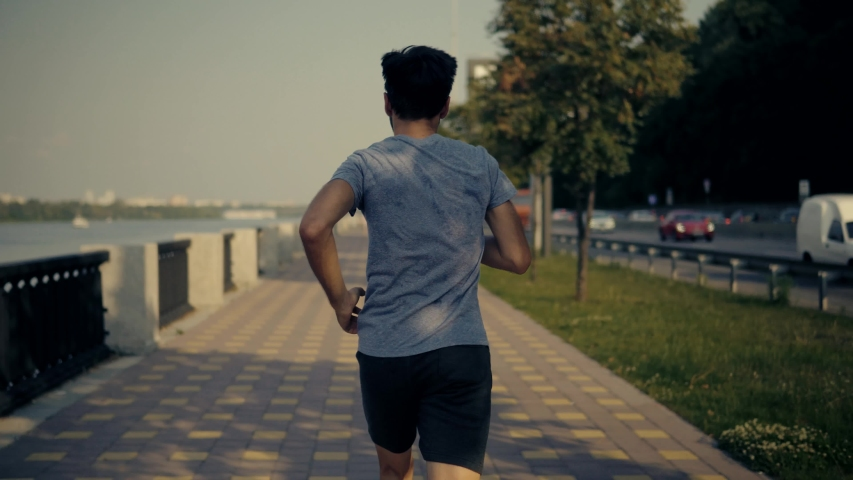 Sportsman Jog Cardio Workout.Runner Fitness Hard Training Before Running Marathon  Competition.Running Man Fitness Exercising.Athlete Jogging In City,Preparing Triathlon.Sport Healthy Lifestyle