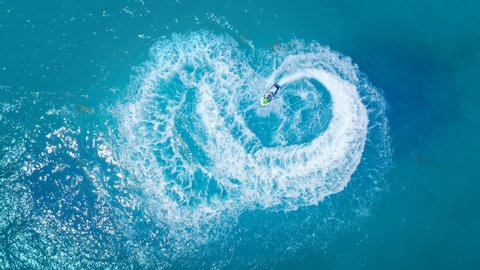 Amazing summer shot of young woman enjoying summer vacation in the Ocean on a personal watercraft. Aerial view of woman racing on a water scooter in crystal clear water in 4K