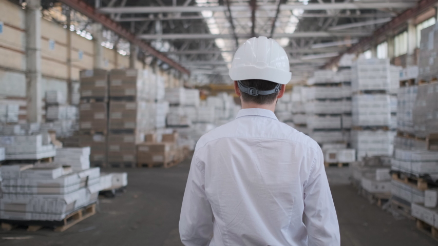 Follow footage of employees male warehouse worker engineer in hard hat working. walking through logistics center warehouse factory construction site logistics architect businessman man builder indoors | Shutterstock HD Video #1035549548