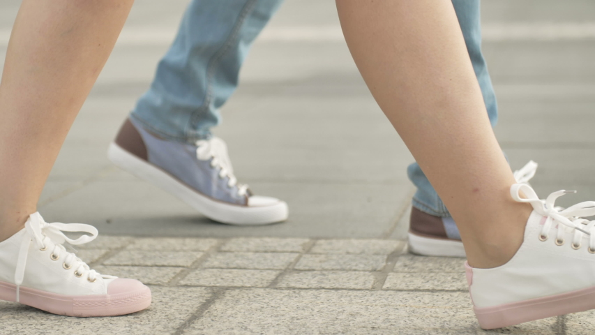 Legs of man and woman. Loving couple embracing at sunset, walking in city   Shutterstock HD Video #1035556994