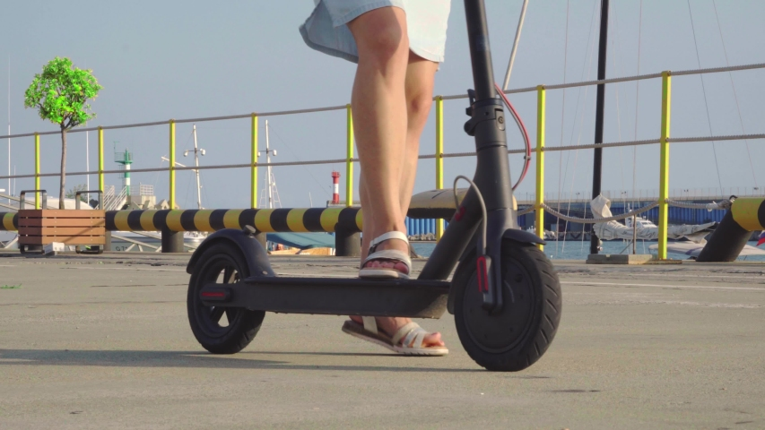 The girl gets up and starts riding an electro scooter. Portrait of a modern girl on a scooter. Girl's feet on scooter. Close up.   Shutterstock HD Video #1035567896