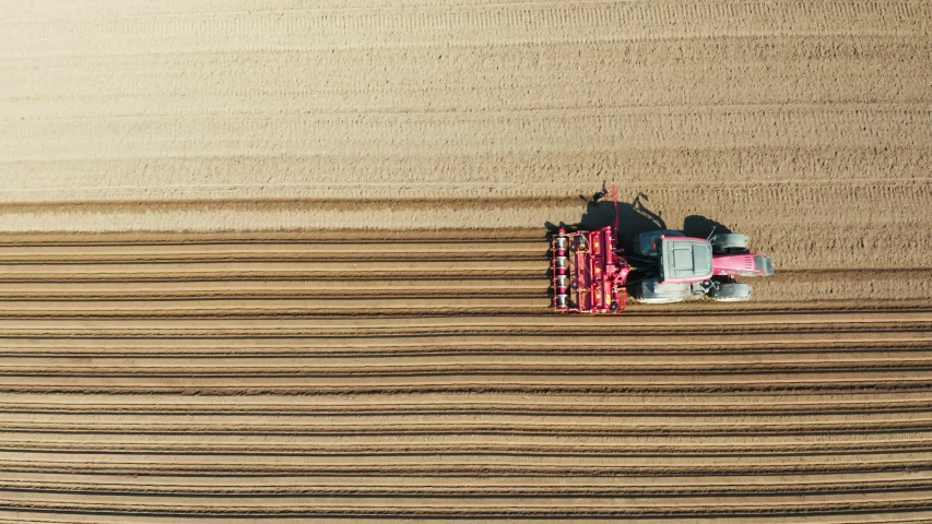 Aerial view tractor cuts furrows in farm field for sowing farm tractor with rotary harrow plow preparing land for sowing. Tractor with harrows prepares the agricultural land for planting crop