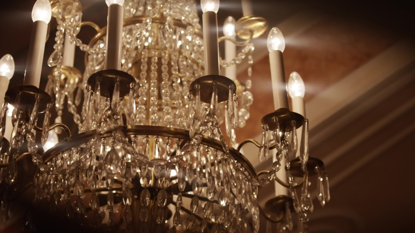 Rich Chandelier in a victorian hotel -  Nice Lenseflares of a RED Dragon Camera, open aperture | Shutterstock HD Video #1035570539