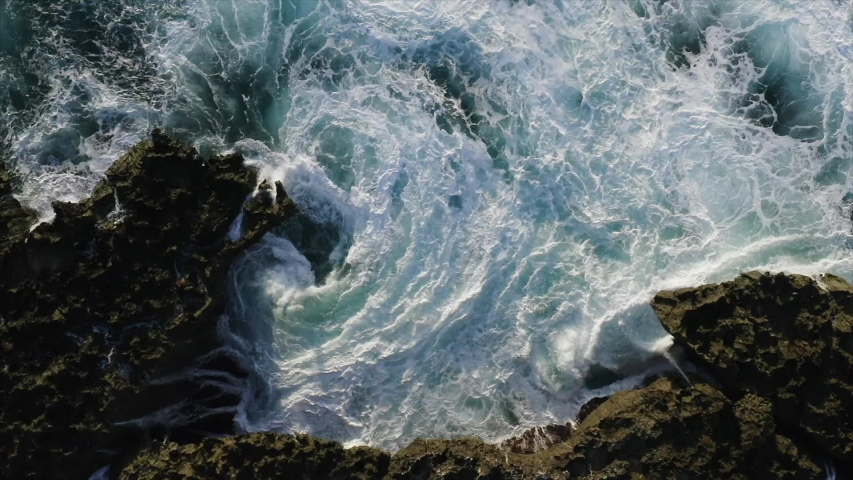 Breathtaking top aerial slow motion view of azure ocean and giant waves crashing at rocky cliff with splashing and white foam. Bali island, Indonesia Royalty-Free Stock Footage #1035582608