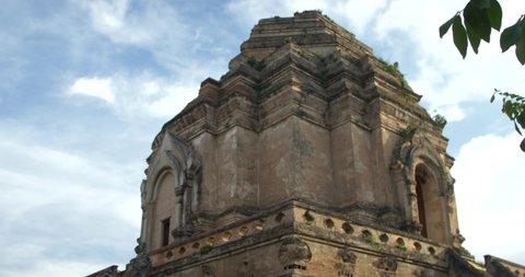 Tilt shot and view of Wat Chedi Luang behind tree, Chiang Mai