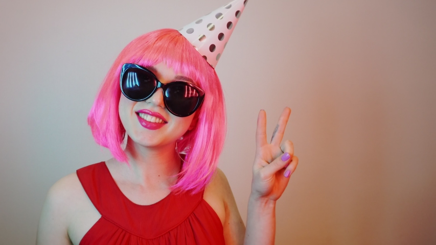 Woman in a pink bright wig at a party. She is dancing and having fun. Close-up of the face. #1035592457