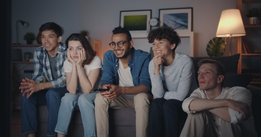 Joyful students watching funny comedy on TV at night laughing having fun in cozy dark room. Friendship, modern entertainment and youth lifestyle concept.