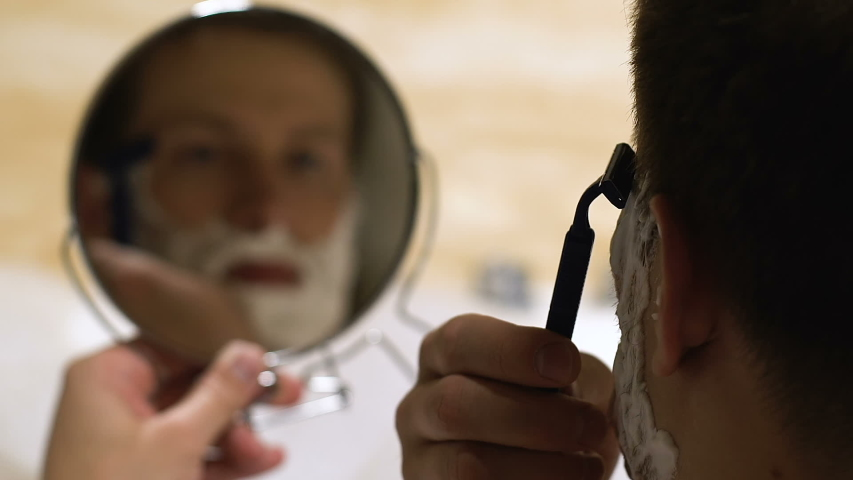 Young handsome male shaving in bath holding mirror, everyday skincare rituals #1035609884