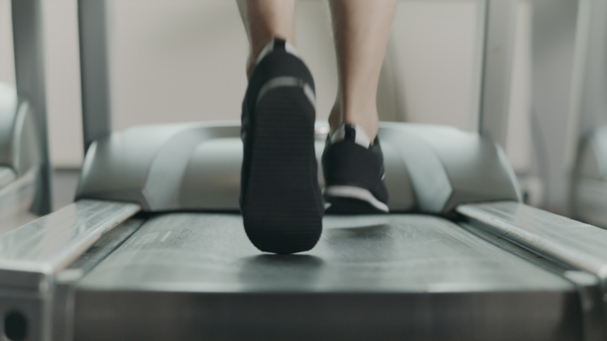 Closeup athletic feet running on treadmill in fitness gym. Back view of black shoes having workout on treadmill. Low view sneakers training in sport club. Royalty-Free Stock Footage #1035619697