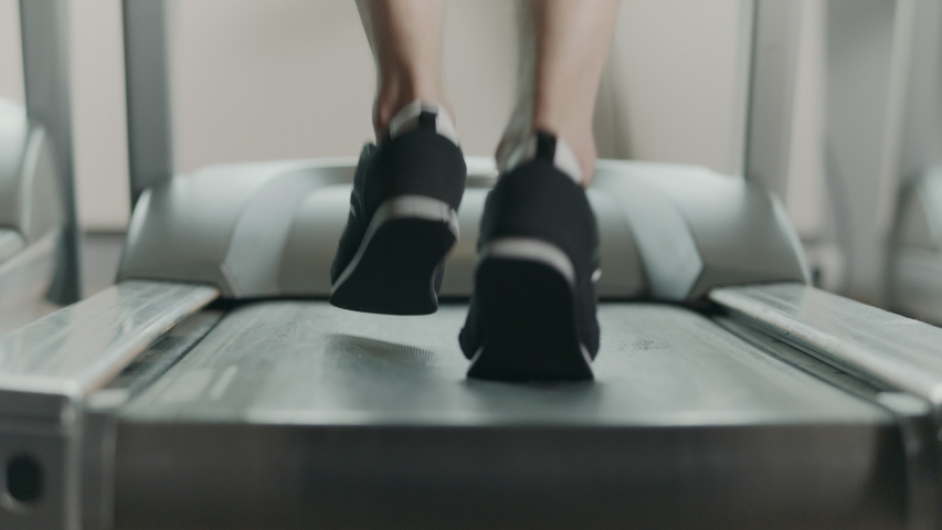 Closeup feet starting run on treadmill in fitness gym. Back view of black shoes training on treadmill. Low view jogging training in sport club. | Shutterstock HD Video #1035619733