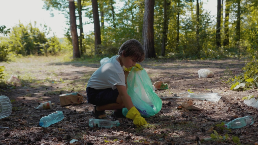Close up voluteers activists child in gloves tidying up rubbish in park or forest save environment stop plastic pollution bag bottle recycle ecology garbage nature altruism care clean slow motion | Shutterstock HD Video #1035620009