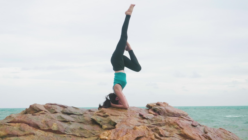 Asian woman training young girl practicing yoga on mountain background sky and ocean,Healthy active lifestyle concept #1035632312