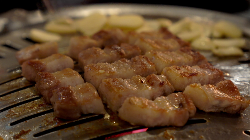 4K Close up shot of chef hand cooking korean charcoal smoked grilled pork belly meat on iron grill pan in korean restaurant. Korean BBQ, food and drink concept.