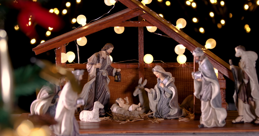 Jesus Christ Nativity scene with atmospheric lights near Christmas tree. Christmas scene. Focus is moving from Christmas tree to manger. Dolly shot 4k
