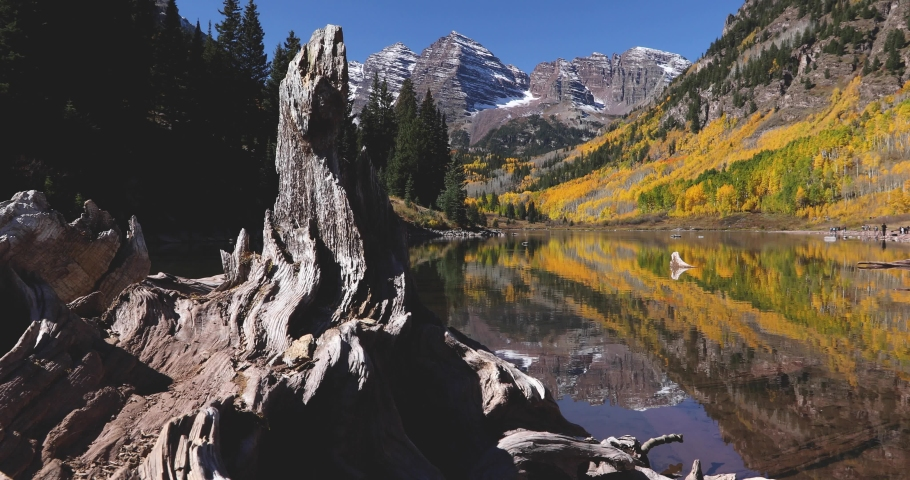 Maroon Bells Aspen Colorado. The Rocky Mountains reflect perfectly in Maroon Lake during peak fall colors. Motion shot, 4K footage shot on a cinema slider.