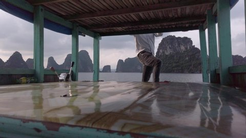 View From foredeck, Fisherman on traditional wooden boat sailing on emerald water in Halong Bay, Vietnam. Impressive background with limestone covered by rainforest jungle. No face.