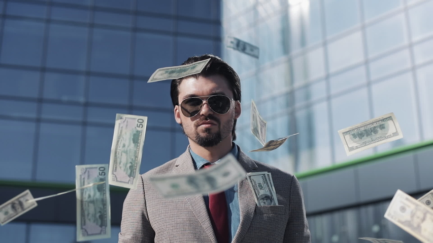 Young Successful Businessman in a Suit Wear Sunglasses Throwing Money in the Camera Standing in the Street near Office Building. Money rain, falling dollars. Successful business concept.