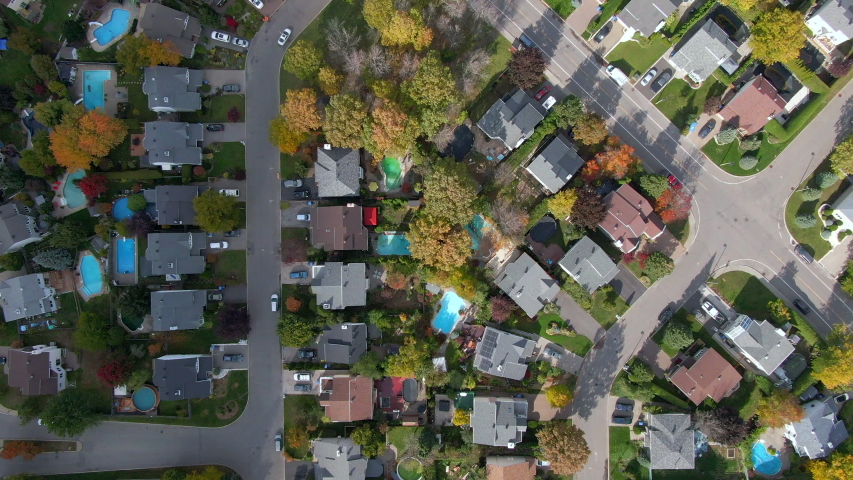 Fall in Montreal, Quebec, Canada, top-down aerial view of residential neighbourhood showing family homes and maple trees changing colour in Autumn season.