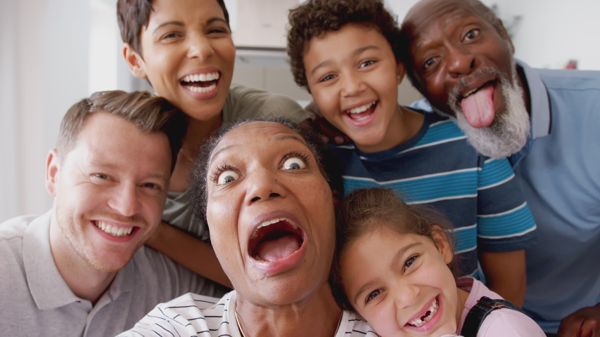 POV Shot Of Multi-Generation Mixed Race Family Posing For Selfie At Home Together #1035656864