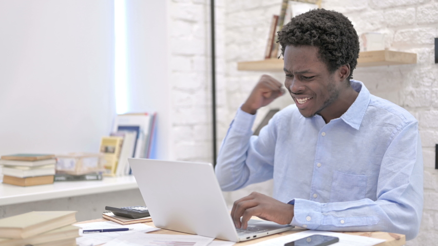 Surprised Young African Man working on laptop #1035670268