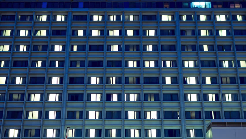 4K 30p Day to night transition timelapse view of the face of a big city hospital.Room lights blinking and patient activity from the outside.