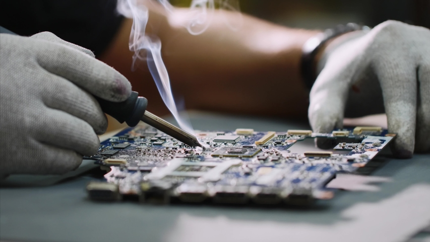 Technician engineer in workshop. Repairman in gloves is soldering circuit board of electronic device on the table, hands close up. He takes tin with a soldering iron and puts it on microcircuit. Royalty-Free Stock Footage #1035701201