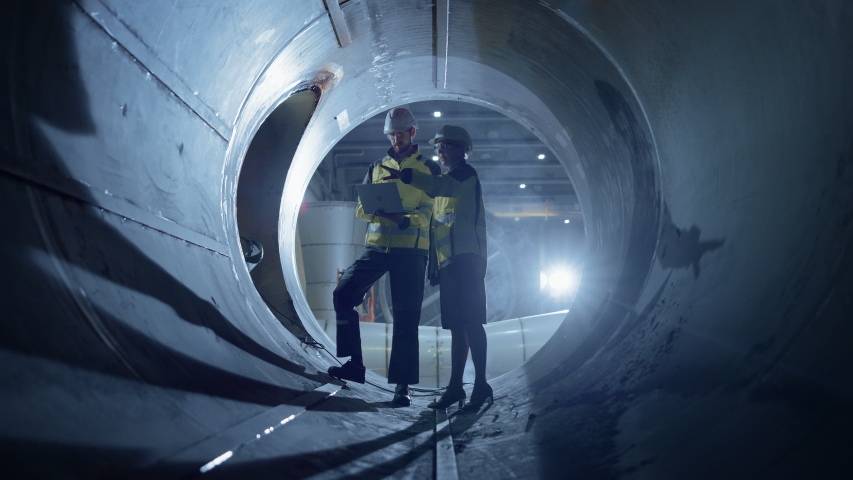 Two Heavy Industry Engineers Walking Inside Pipe, Use Laptop, Have Discussion, Checking Design. Construction of the Oil, Natural Gas and Biofuels Transport Pipeline. Industrial Manufacturing Factory | Shutterstock HD Video #1035703964