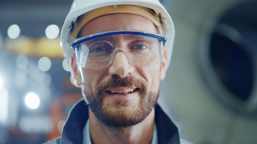 Portrait of Smiling Professional Heavy Industry Engineer / Worker Wearing Safety Uniform, Goggles and Hard Hat. In the Background Unfocused Large Industrial Factory | Shutterstock HD Video #1035703994